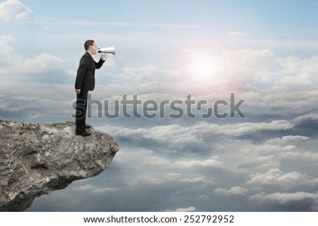 Businessman using megaphone yelling on cliff with sunlight cloudscape background - stock photo