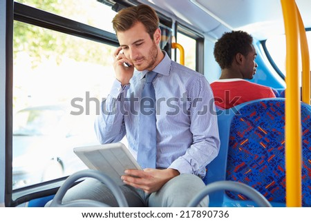 Businessman Using Mobile Phone And Digital Tablet On Bus - stock photo