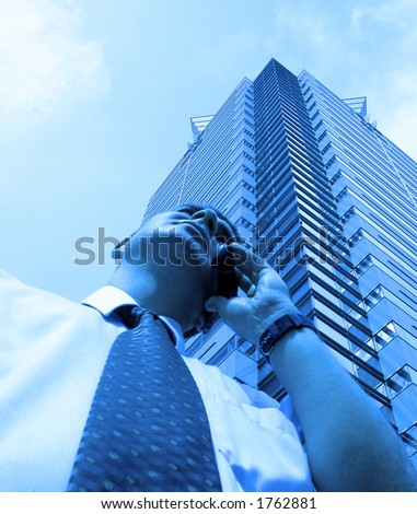 Businessman using mobile phone in a big city. Soft focus on the man. - stock photo