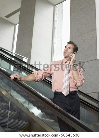 Businessman using mobile phone on escalator - stock photo
