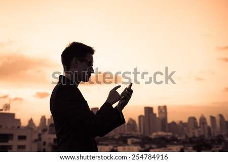 Businessman using mobile smart phone in the city - stock photo