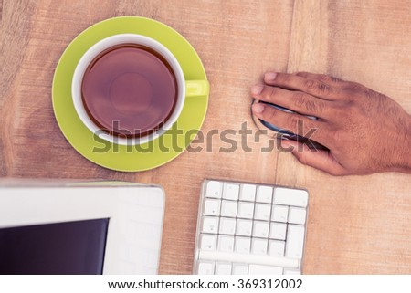 Businessman using mouse while working at table in office - stock photo
