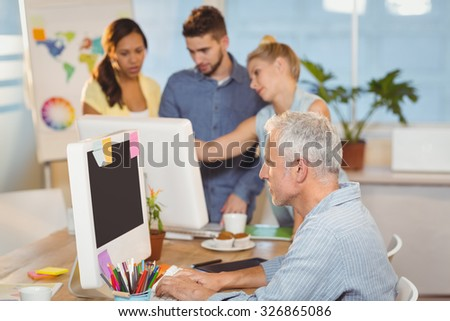 Businessman using on computer with colleagues working in background in creative office - stock photo