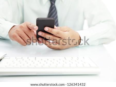 Businessman using phone on the desk - stock photo
