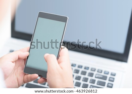Businessman using smart phone and laptop.