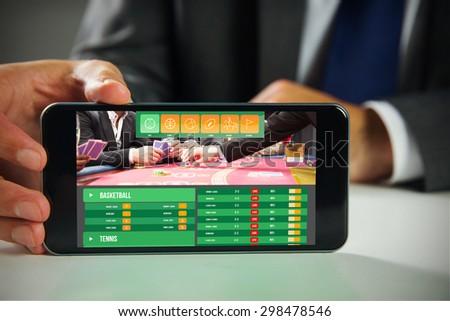 Businessman using smartphone against gambling app screen - stock photo