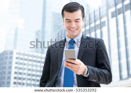 Businessman using smartphone in front of office buildings in the city