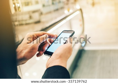 Businessman using smartphone on the escalator, with flare effect - stock photo