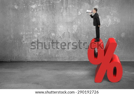 Businessman using speaker yelling on red percentage sign with concrete room background - stock photo