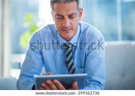 Businessman using tablet computer in living room