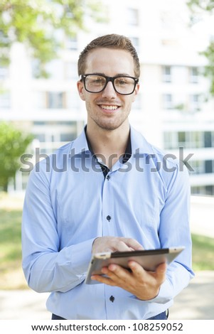 Businessman Using Tablet Computer in park - stock photo