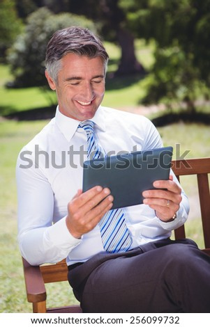 Businessman using tablet in the park on a sunny day