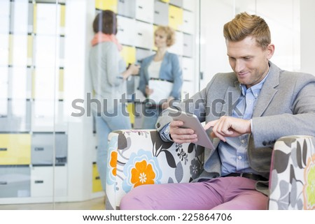 Businessman using tablet PC with colleagues discussing in background at creative office - stock photo