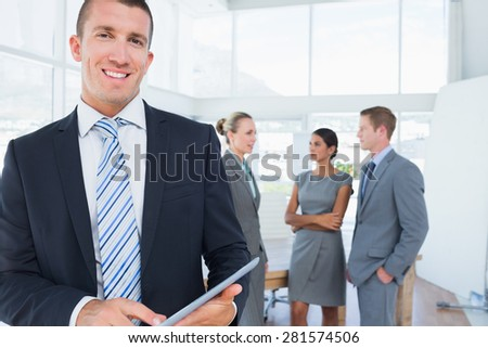 Businessman using tablet with colleagues behind him in the office