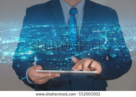 businessman using tablet with night modern city background