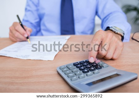 Businessman using the calculator while writing in the office - stock photo