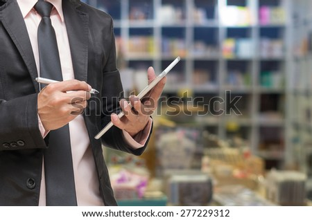 Businessman using the tablet on Abstract blurred photo of book store background - stock photo