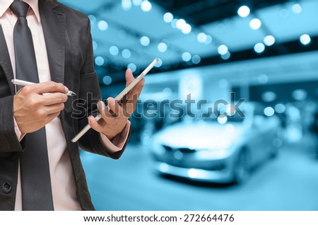 Businessman using the tablet on abstract blurred photo of motor show background,blue color tone - stock photo
