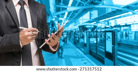 Businessman using the tablet on Abstract blurred photo of sky train station with people background, blue color tone - stock photo