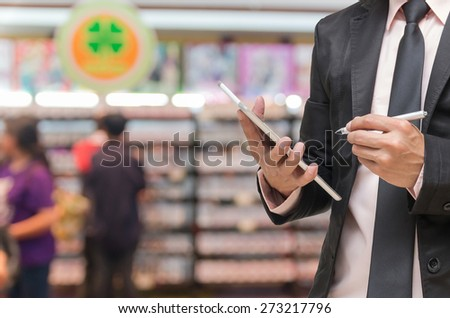 Businessman using the tablet on on Abstract blurred photo of book store with people background - stock photo