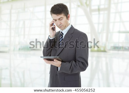 businessman using touch pad of tablet pc, on the phone, at the office - stock photo