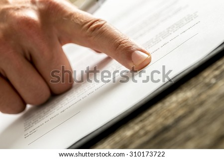 Businessman waiting for a signature on a contract or deal pointing with his finger to the correct place to sign, close up low angle view of the document and his finger. - stock photo