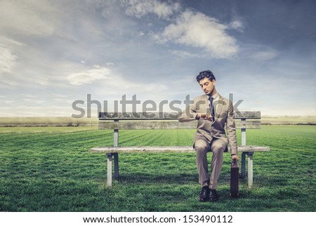 businessman waiting sitting on a park bench in countryside - stock photo