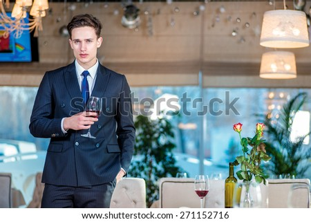 Businessman waits for the main meeting. Confident businessman in formal wear standing in a restaurant while holding a glass of wine and looking at the camera - stock photo