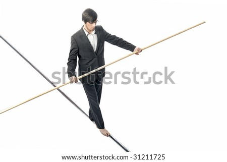 Businessman walking a tightrope - isolated on white - stock photo