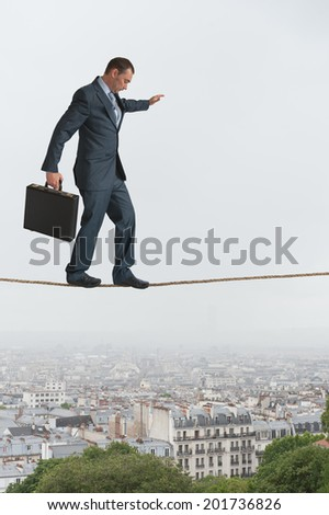 businessman walking across a tightrope above a city - stock photo