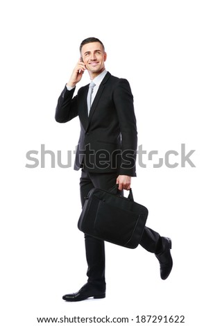 Businessman walking and talking on the phone over white background - stock photo