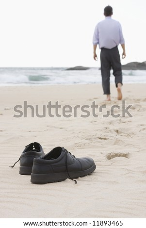 Businessman walking barefoot on a beach. Focus on his shoes in the foreground. - stock photo
