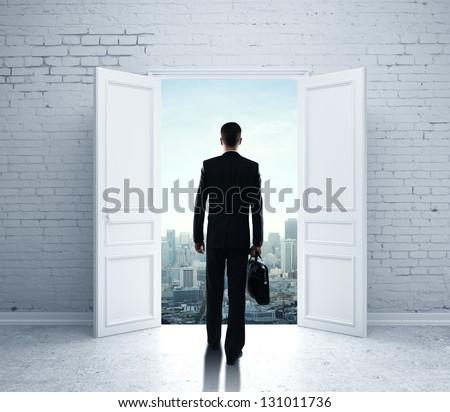 businessman walking in open door to city - stock photo