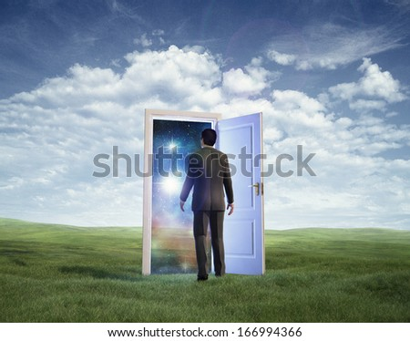 Businessman walking in open door to galaxy - stock photo