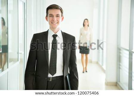 Businessman walking in the office corridor - stock photo