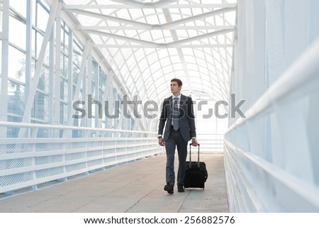 Businessman walking in urban environment of airport with suitcase - stock photo