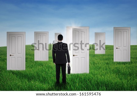 Businessman walking into opportunity doors on the green field - stock photo