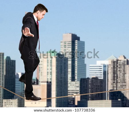 Businessman walking on a rope - stock photo