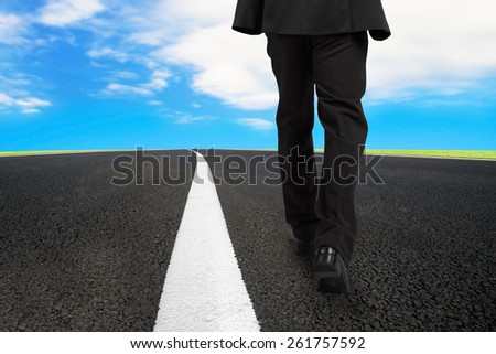 Businessman walking on asphalt road with white line and sky clouds - stock photo