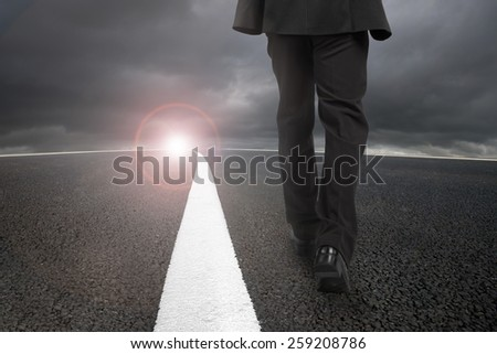 Businessman walking on asphalt road with white line and sunlight cloudy sky - stock photo