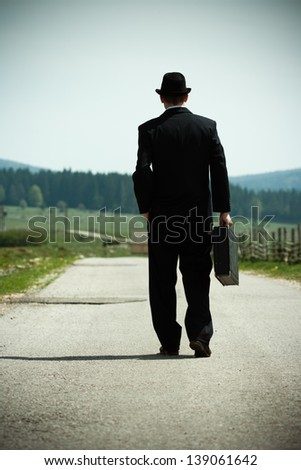 Businessman walking on country road and thinking,Time for contemplation - stock photo