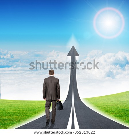 Businessman walking on freeway road going up in sky, rear view