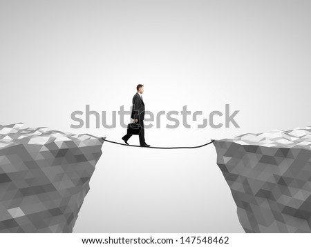 businessman walking on rope from mountain to mountain - stock photo