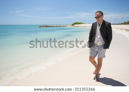 Businessman walking on the beach - stock photo