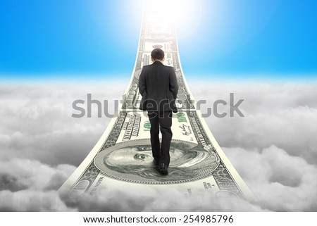 Businessman walking on the money stairs with blue sky sunlight cloudscape background - stock photo