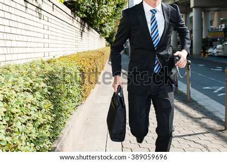 Businessman walking on the sidewalk