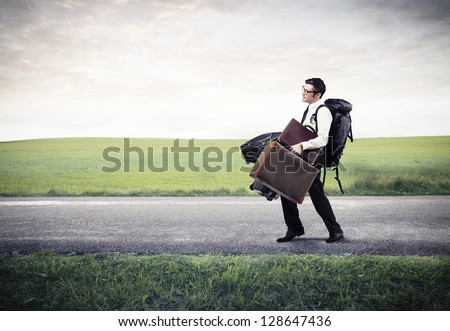 businessman walking on the street with a lot of luggage - stock photo