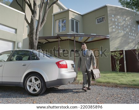 Businessman walking out to his car - stock photo