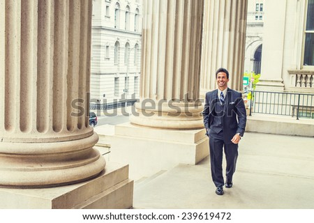 Businessman walking to work. Dressing in dark blue three piece suit, necktie, leather shoes, a handsome, sexy, middle age business man is waking passed by columns outside an office building. - stock photo