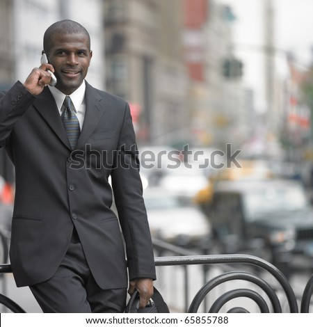 Businessman walking while talking on cell phone - stock photo